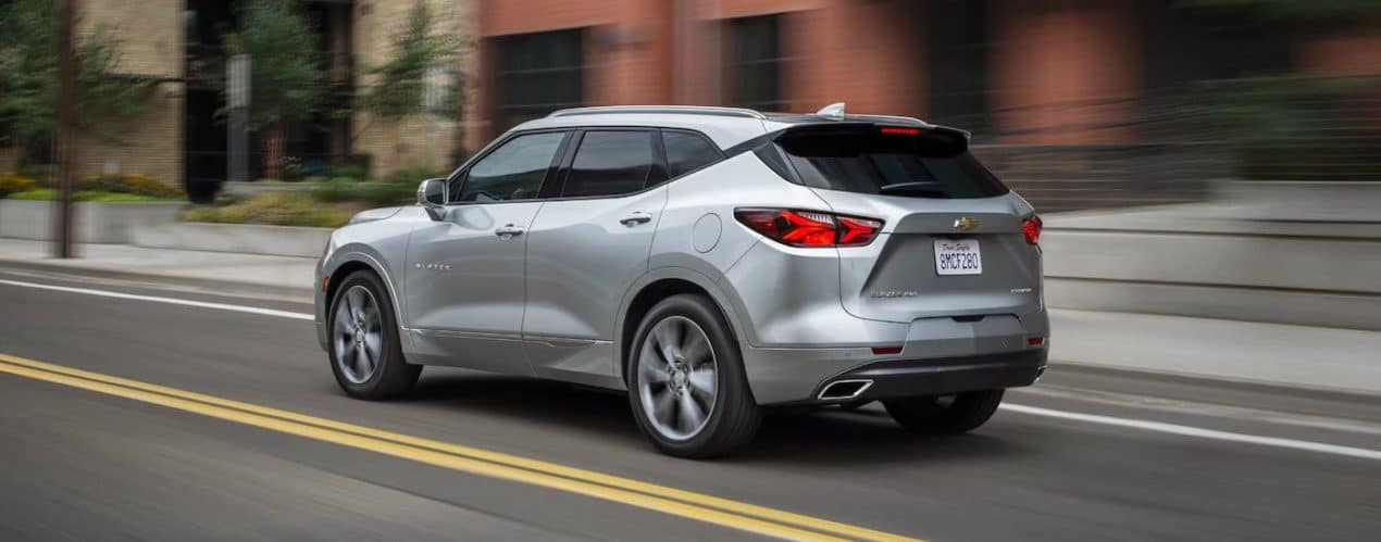 A silver 2021 Chevy Blazer is shown from the rear three-quarters while driving on a city street.