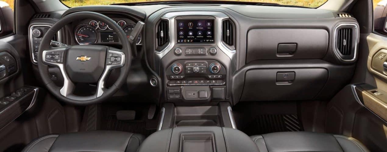 The dashboard and gray interior of a 2021 Chevy Silverado 1500 are shown.