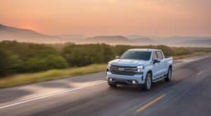 A white 2021 Chevy Silverado High Country is driving down the road.