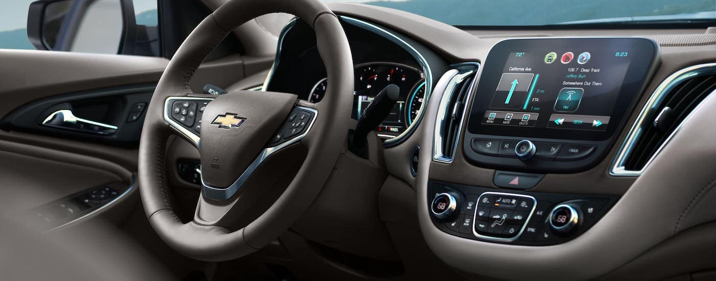 The brown steering wheel and infotainment center in a 2017 used Chevy Malibu are shown.
