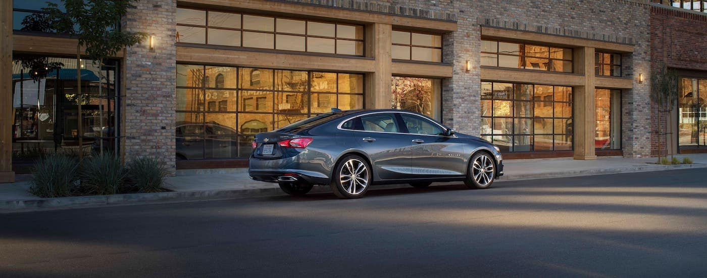 A gray 2019 used Chevy Malibu is parked in front of a tan brick building.