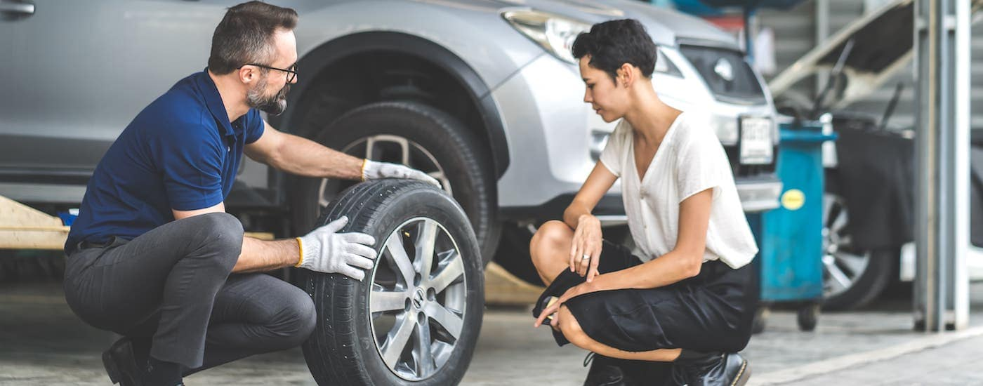 A mechanic is showing a woman a tire in front of a silver SUV.