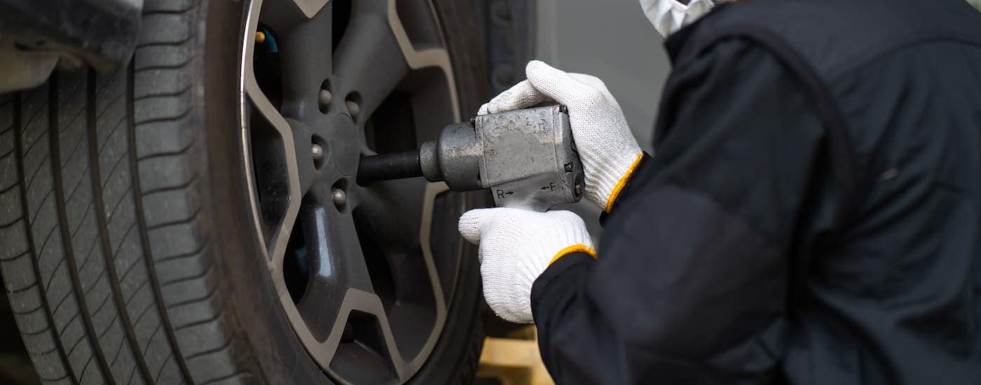 A mechanic is using an impact wrench on a tire that is on a lift.