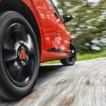 A close up is shown of a red car with black wheels driving down a blurred road.