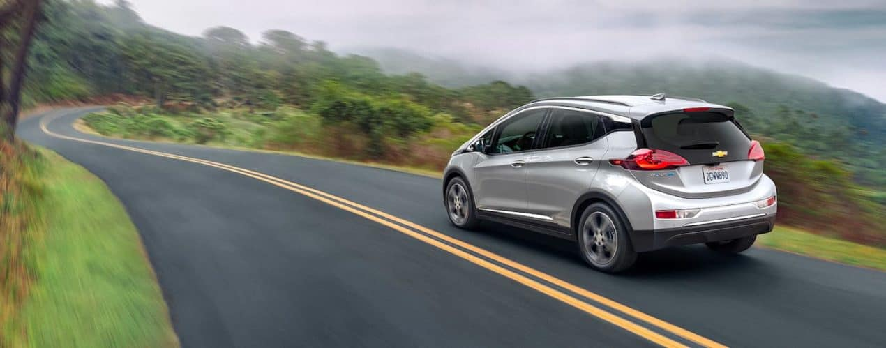 A silver 2021 Chevy Bolt EV is driving down a misty road.