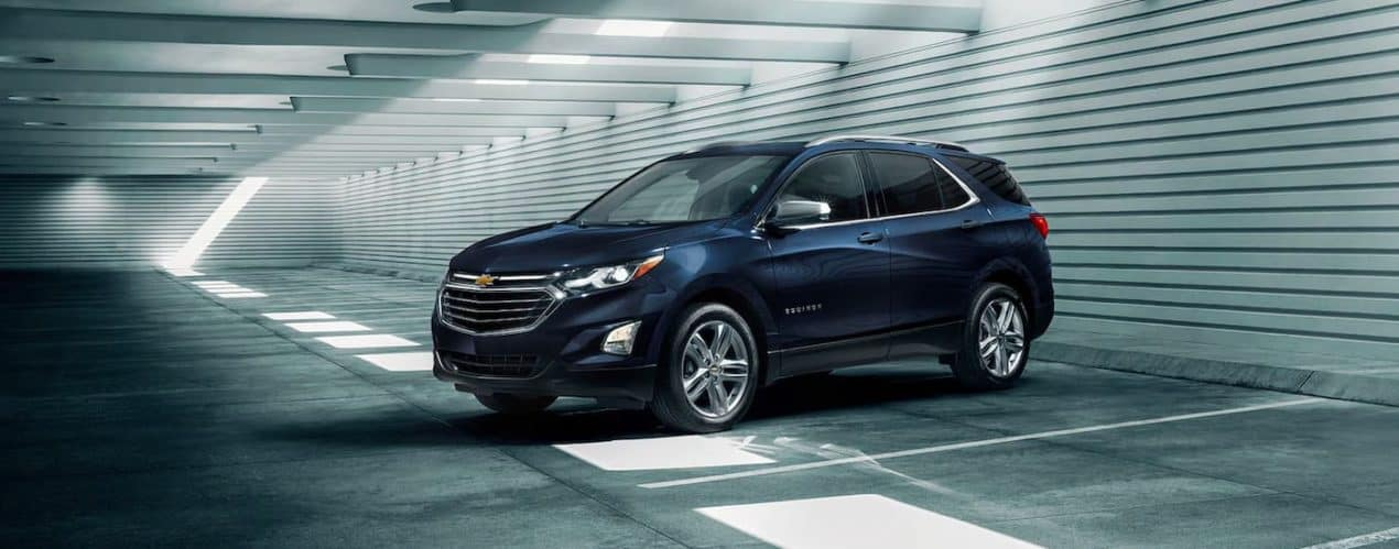 A dark blue 2021 Chevy Equinox is shown from the side while parked in an empty parking garage.