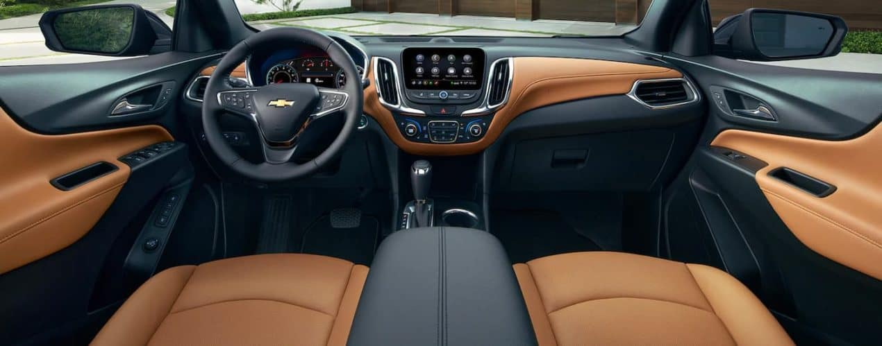 The front brown and black interior is shown from the back seat on a 2021 Chevy Equinox.
