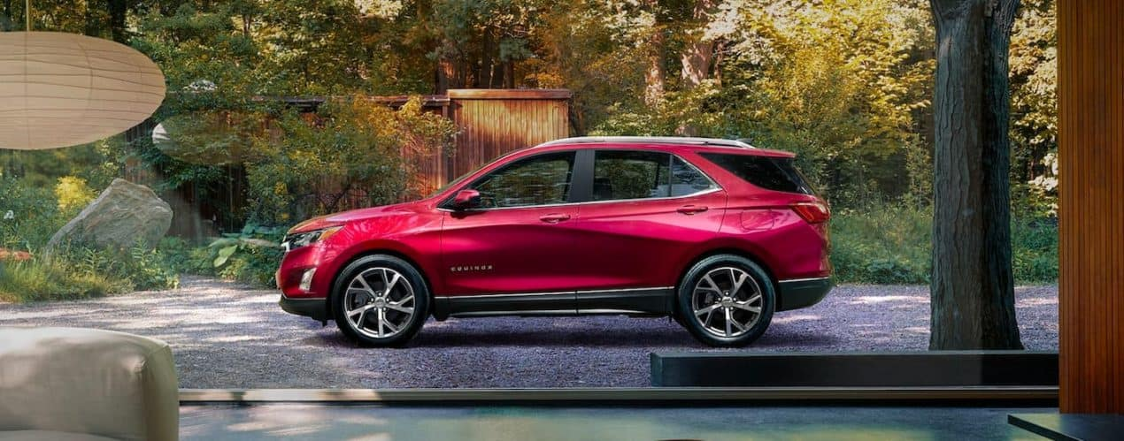 A red 2021 Chevy Equinox is shown from the side while parked in a driveway next to a wooden shed.