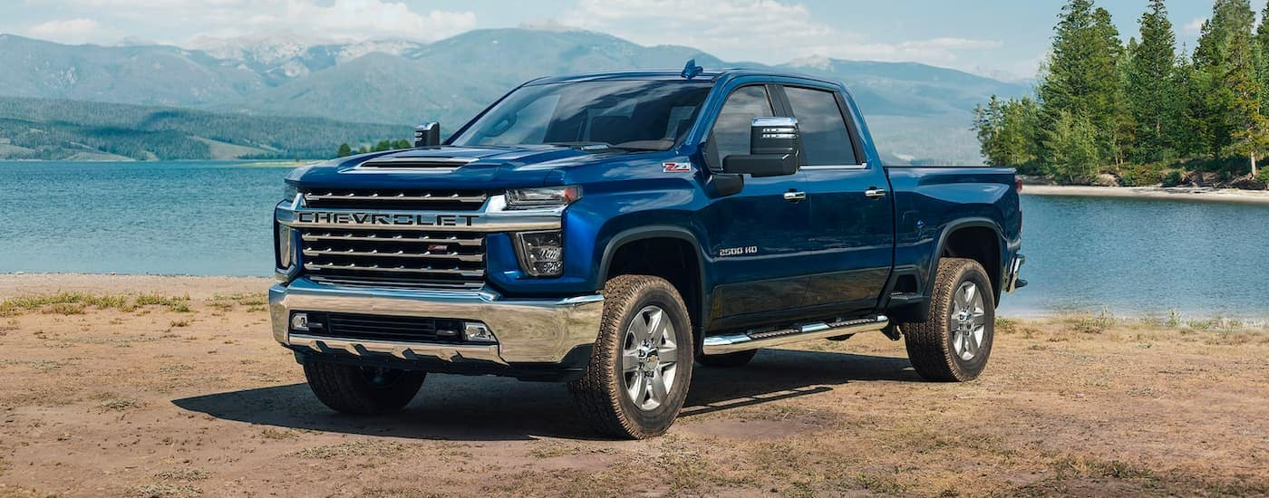 A blue 2021 Chevy Silverado 2500 HD is parked on a dirt shore with a lake in the background.