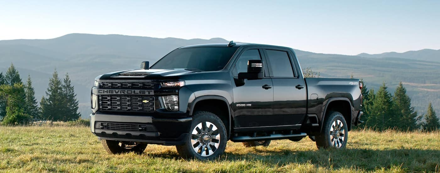A black 2021 Chevy Silverado 2500 HD is parked on the grass with mountains in the distance.