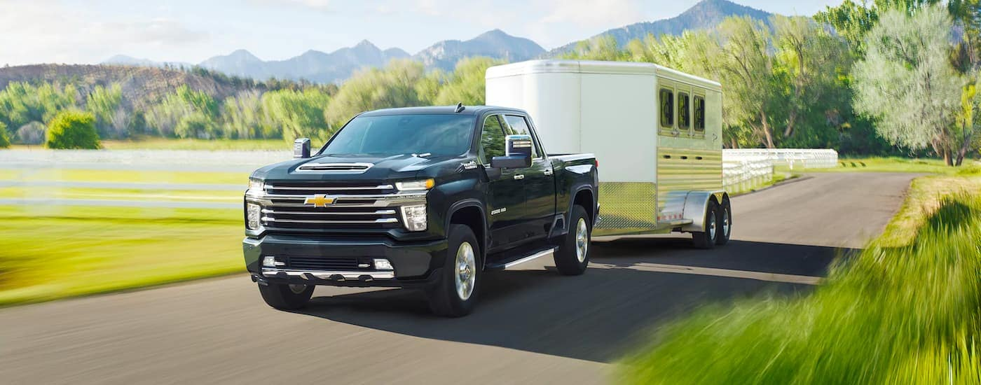 A black 2021 Chevy Silverado 2500 HD is towing a white enclosed horse trailer past a field.