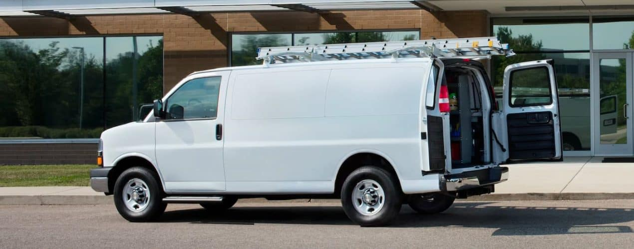 A white 2021 Chevy Express Cargo Van is shown from the side with its rear doors open.