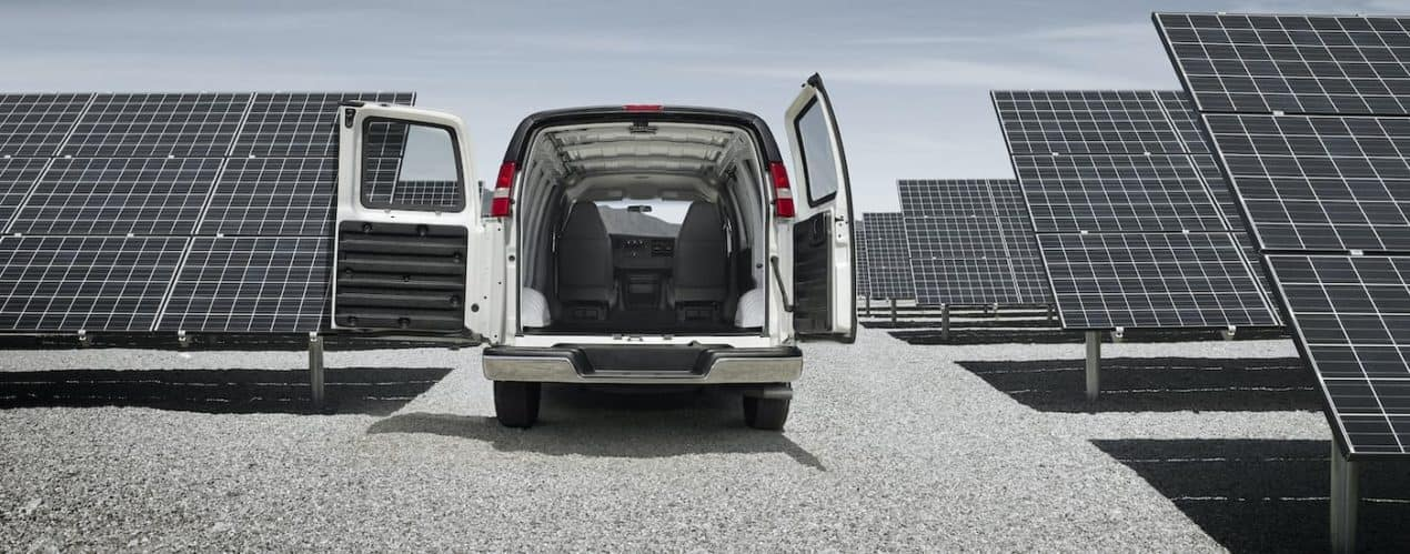 A white 2021 Chevy Express Cargo Van is shown parked in between a row of solar panels.