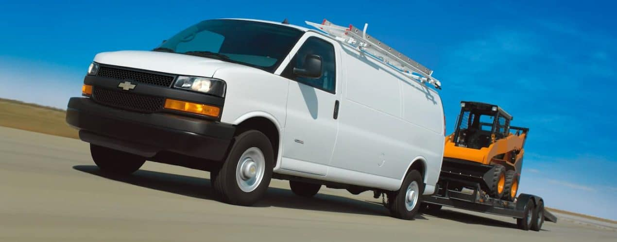 A white 2021 Chevy Express Cargo Van is towing a front loader down the highway.