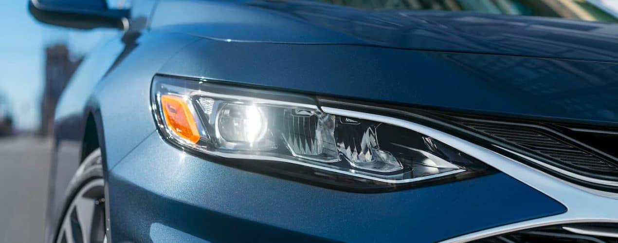 A close up shows the chrome passenger headlight on a 2021 Chevy Malibu.