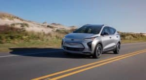 A silver 2022 Chevy Bolt EUV is driving in front of a sandy hill.