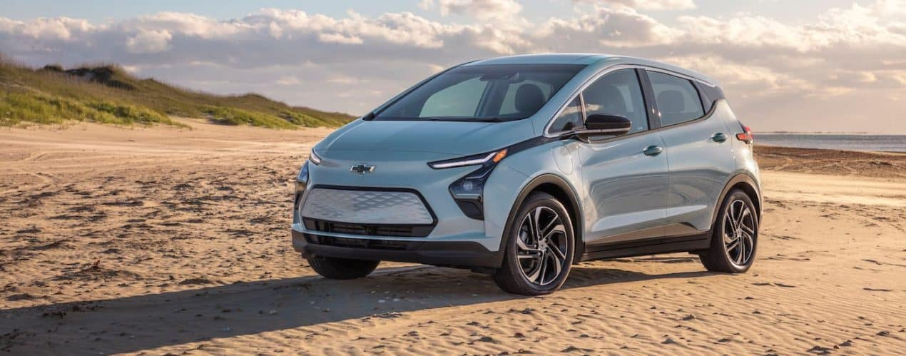 A pale blue 2022 Chevy Bolt EV is parked on a beach.