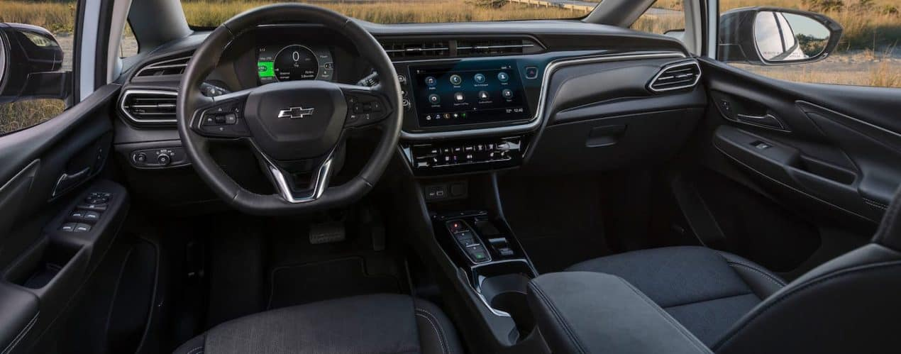 The black dashboard and interior of a 2022 Chevy Bolt EV is shown.