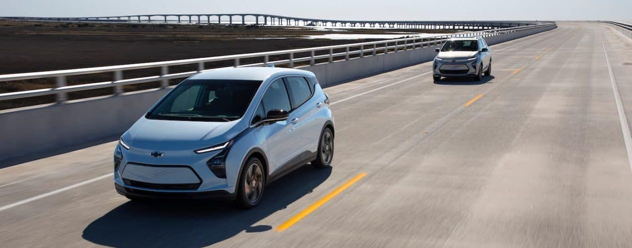 Two pale blue and silver 2022 Chevy Bolt EVs are driving on an empty highway.