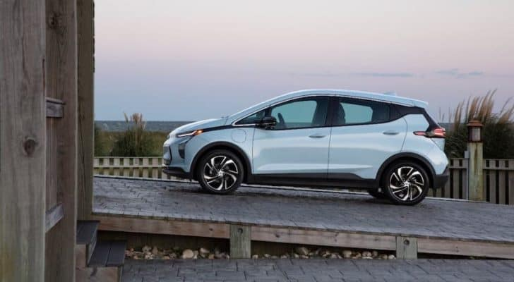 A pale blue 2022 Chevy Bolt EV is shown from the side climbing a ramp in front of a beach.