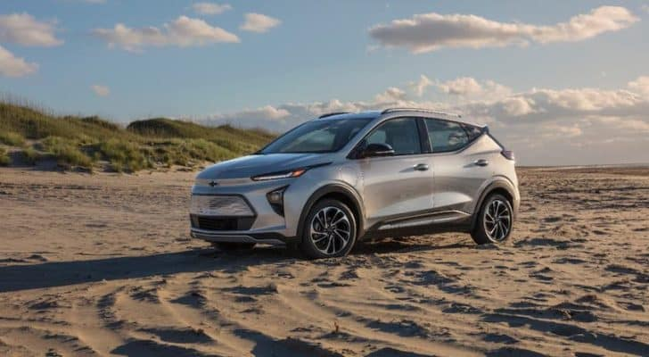 A silver 2022 Chevy Bolt EUV is parked on a beach.