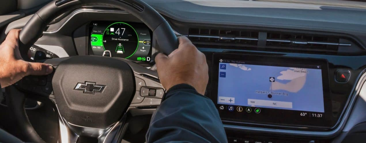 A closeup shows hands on a steering wheel and the infotainment screen in a 2022 Chevy Bolt EUV while driving.