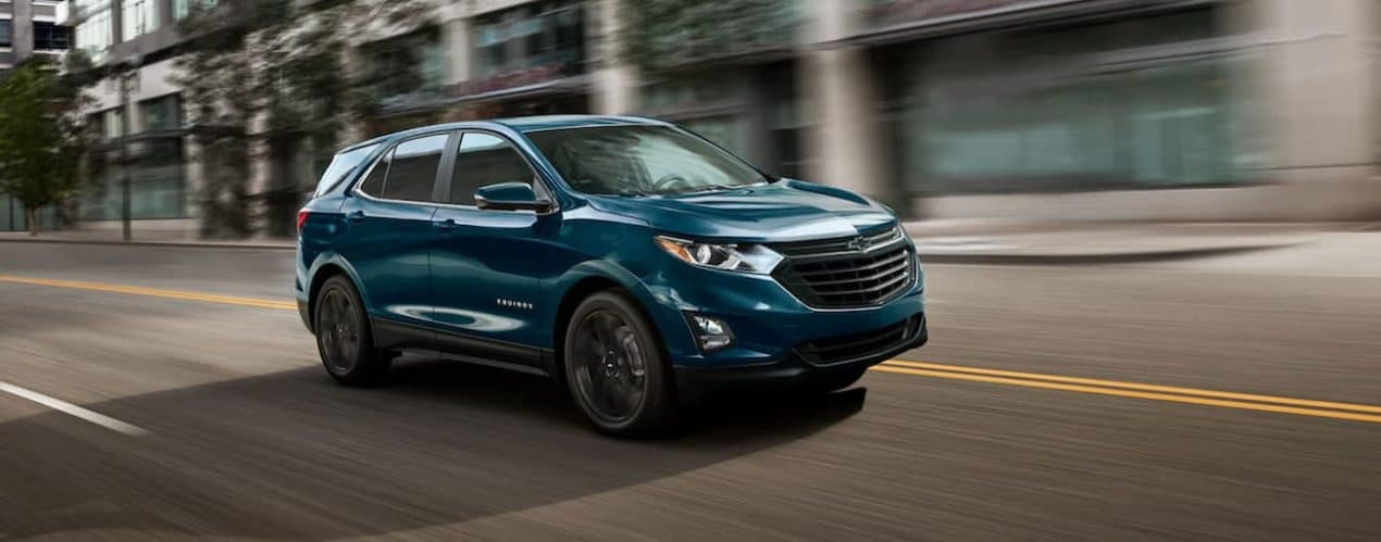 A blue 2021 Chevy Equinox Sport is driving on a city street after winning the 2021 Chevy Equinox vs 2021 Ford Escape comparison.
