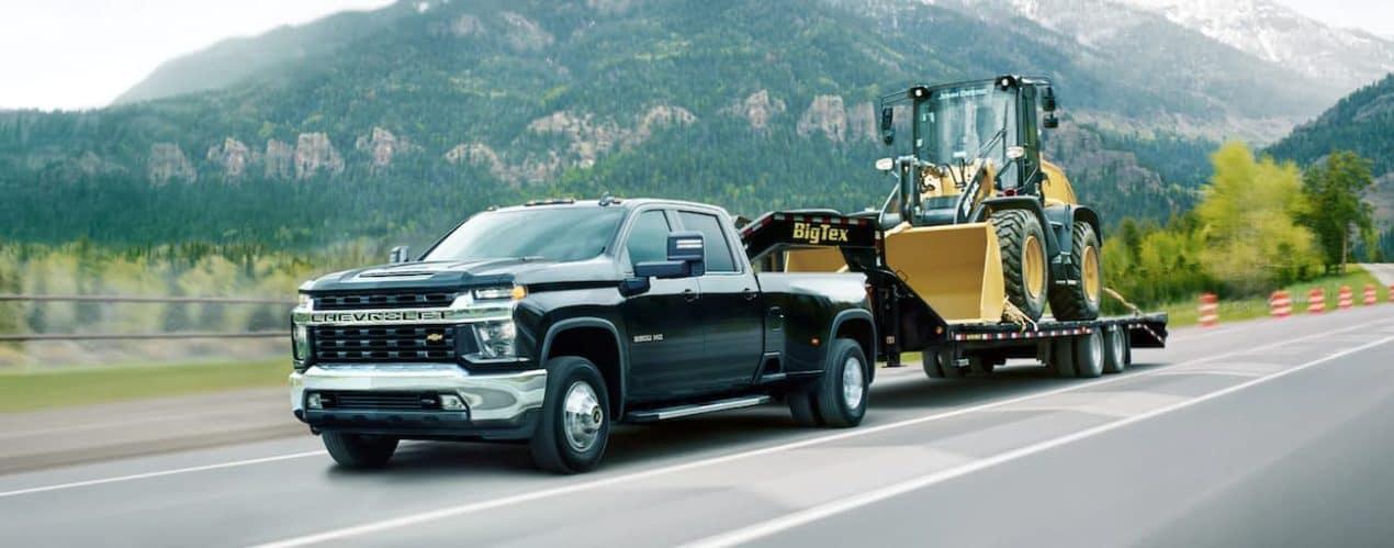 A black 2021 Chevy Silverado 3500 HD is towing construction equipment.