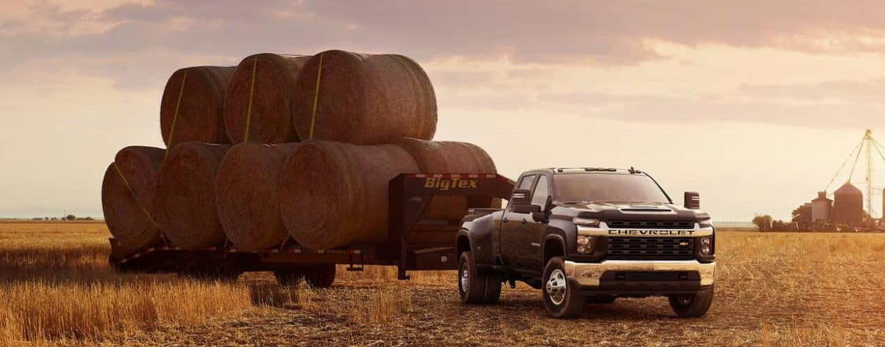 A black 2021 Chevy Silverado 3500 HD is towing a large trailer stacked with hay.