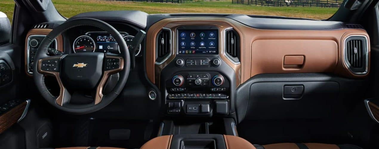 The interior of a 2021 Chevy Silverado 1500 shows the steering wheel and infotainment screen.