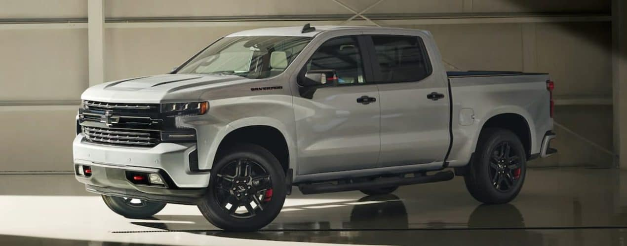 A silver 2021 Chevy Silverado 1500 is parked in a gallery after winning a 2021 Chevy Silverado 1500 vs 2021 Ford F-150 comparison.
