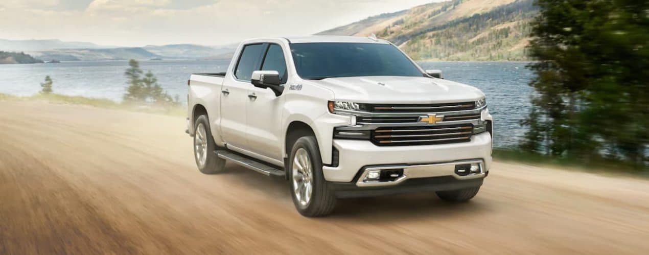 A white 2021 Chevy Silverado 1500 is driving on a dirt road past a lake.