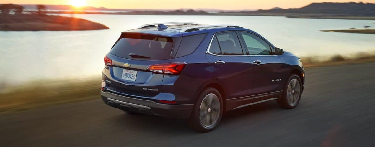 A blue 2022 Chevy Equinox is shown driving past a lake.
