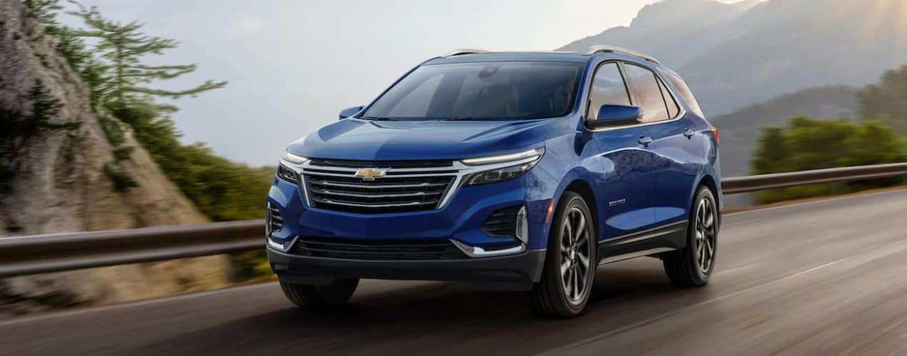 A blue 2022 Chevy Equinox is shown from the front driving on an open road.