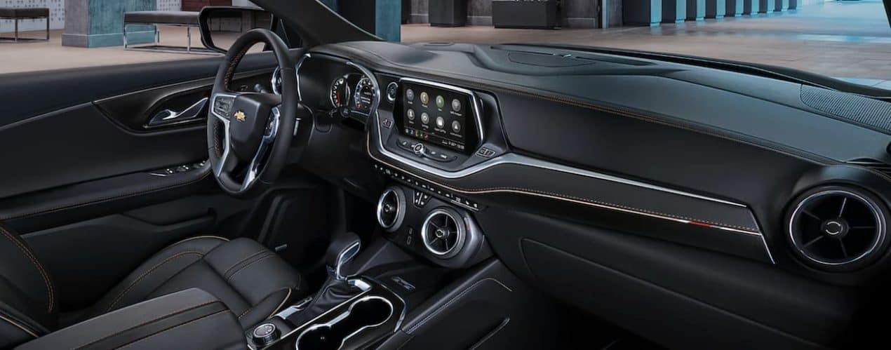 The black interior of a 2022 Chevy Blazer shows the steering wheel and infotainment screen
