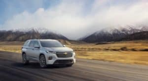 A silver 2022 Chevy Traverse is shown driving on a highway.