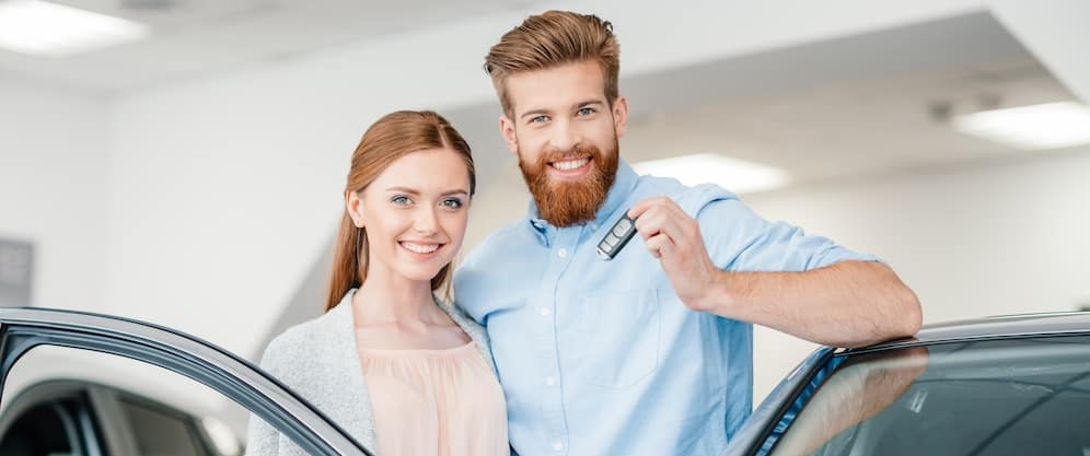 Red haired couple holding car keys and shopping for a used or certified pre-owned vehicle