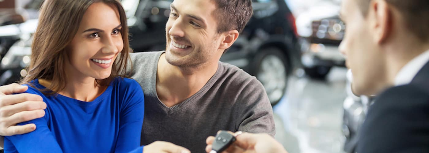 young couple getting keys at dealership