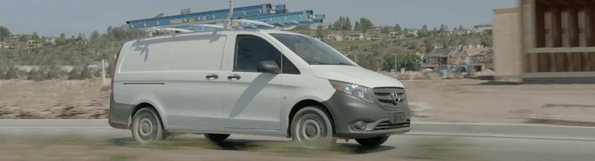 White Metris van driving down a road