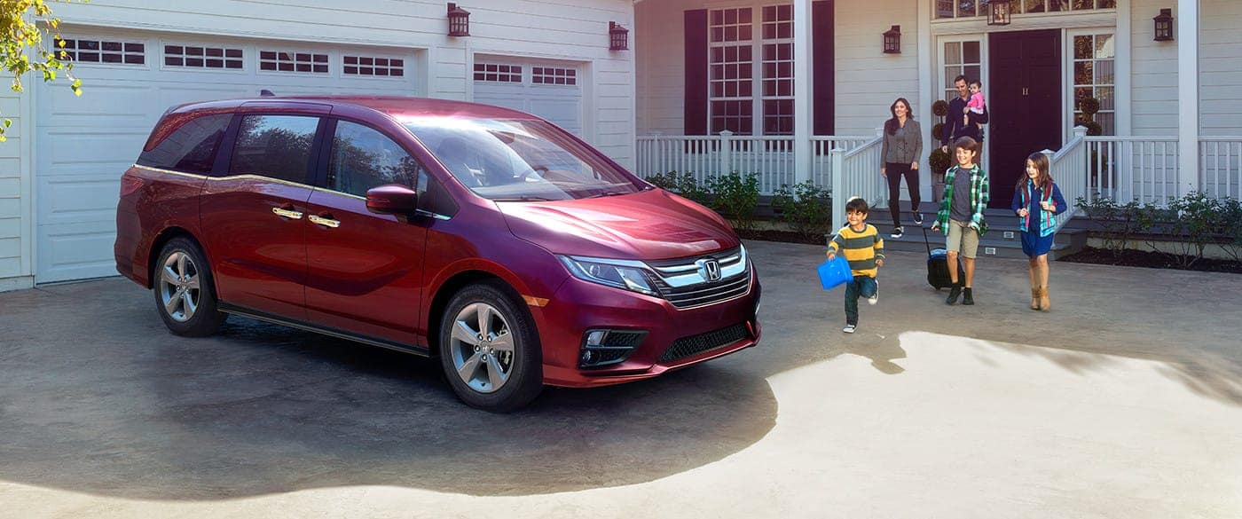 Honda Odyssey parked outside house with family