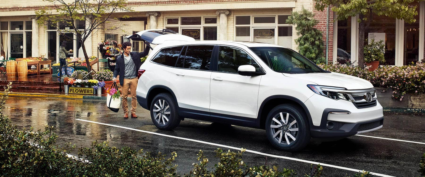 2019 Honda Pilot Parked at store with man loading bags in cargo area