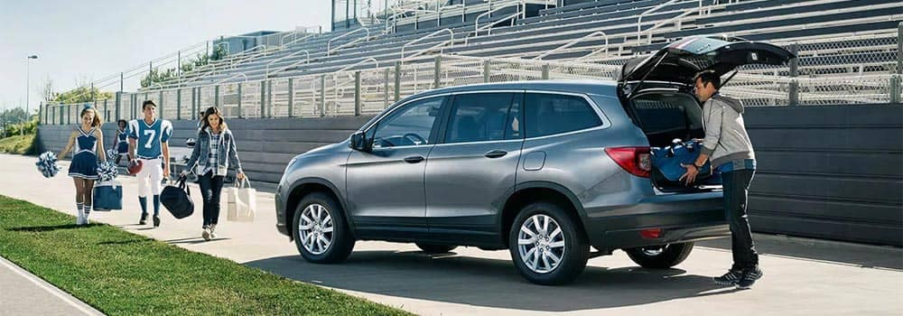 2019 Honda Pilot Parked on Football Field with Family Packing Cargo Area