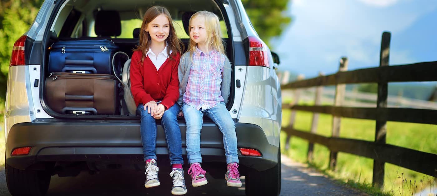 Two little girls sitting in a car before going on vacations with their parents