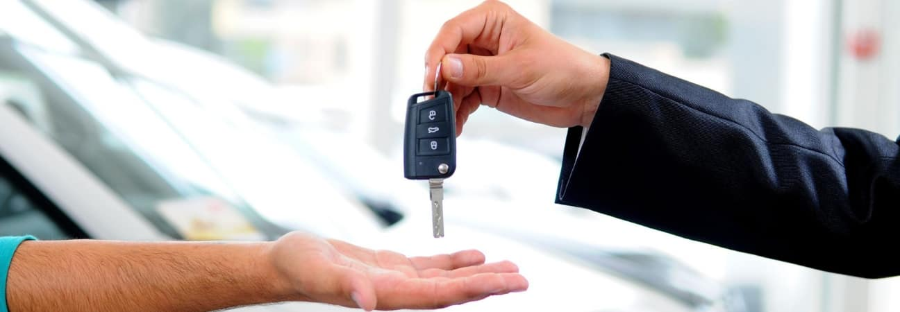 A close up of one person handing keys to another person featured in a blog post about leasing vs financing