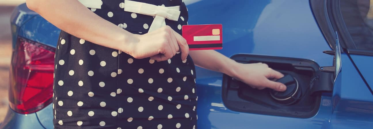 Woman with credit card unscrewing cap on car gas tank