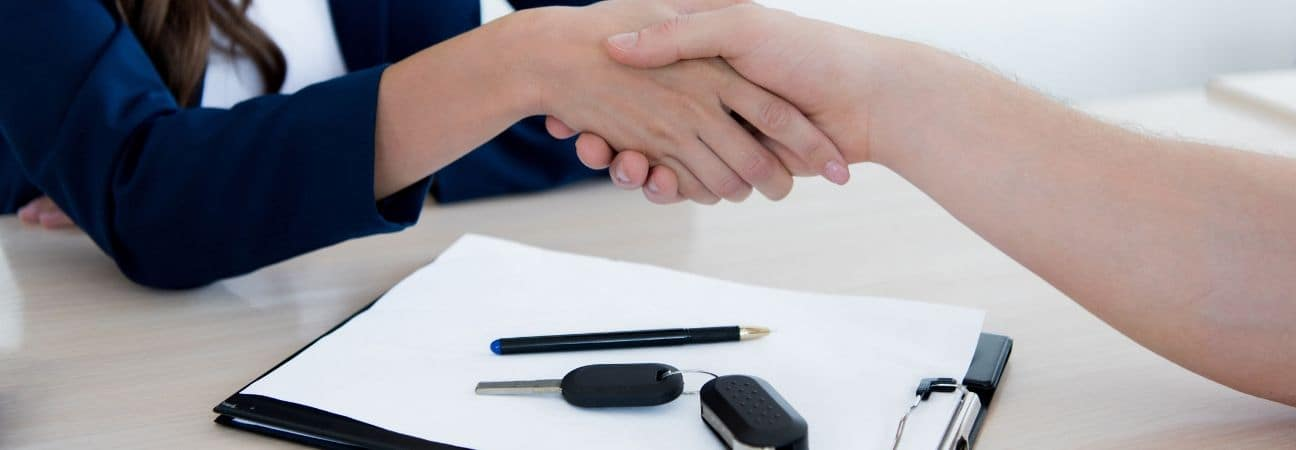 two people in an auto group shaking hands