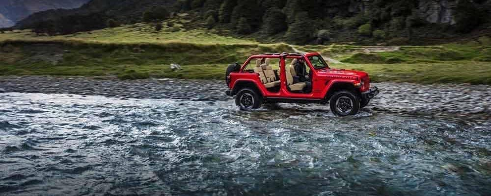 Red Jeep Wrangler With Doors Removed Next to River
