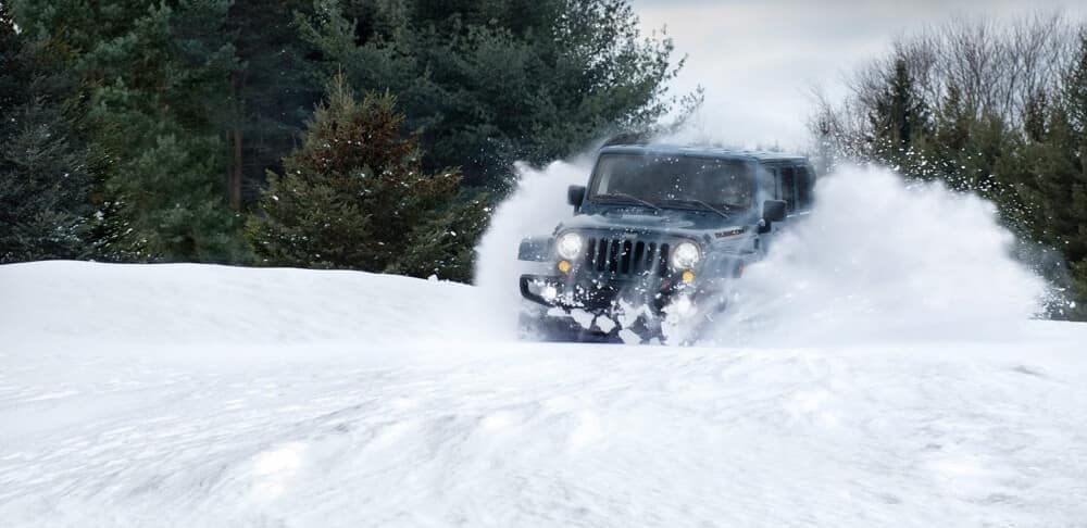 2018 Jeep Wrangler JK bounding through fresh powdered snow