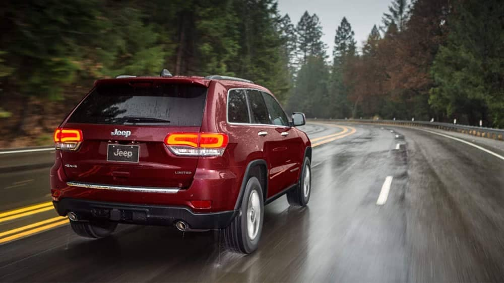 2019 Jeep Grand Cherokee driving through a rain-swept forest