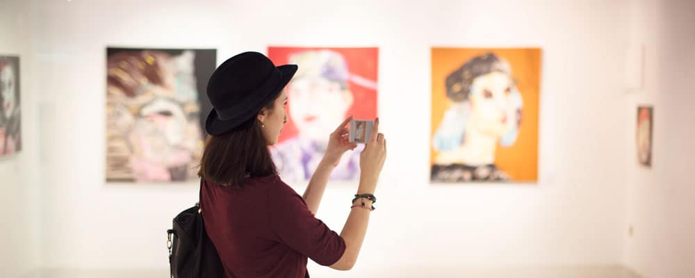 Woman Visiting Art Gallery With Camera